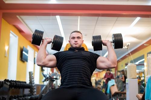 Вдигане на гири за уголемяване на мускулите на гърдите.