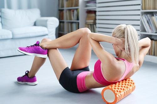 Загрявка за мускулите преди тренировка с тежести с фоумролер.