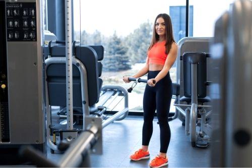 Тяга на хоризонтален блок и на долен блок към корем и към гърди за трениране горната част на тялото в силов фитнес уред.